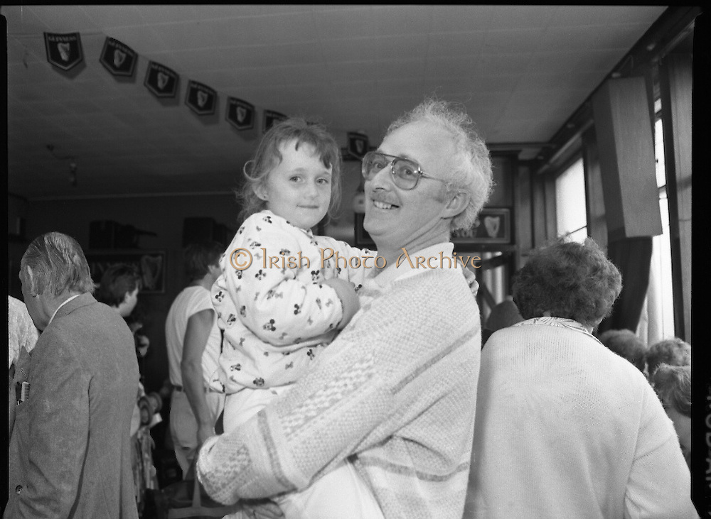 """Guinness Family Day At The Iveagh Gardens. (R83)..1988..02.07.1988..07.02.1988..2nd  July 1988..The family fun day for Guinness employees and their families took place at the Iveagh Gardens today. Top at the bill at the event were """"The Dubliners"""" who treated the crowd to a performance of all their hits. Ireland's penalty hero from Euro 88, Packie Bonner, was on hand to sign autographs for the fans...Dad and daughter pictured enjoying the Guinness family day."""