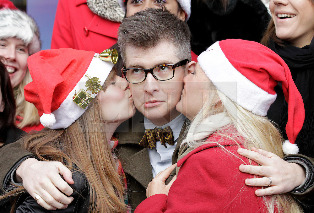 © Licensed to London News Pictures. 20/12/2011. London, United Kingdom .Gareth Malone pulls a silly face as he gets kissed by 2 members of the Military Wives Choir outside of HMV on Oxford Street. The choir sings to the public to celebrate the success of their single..Photo credit : Chris Winter/LNP