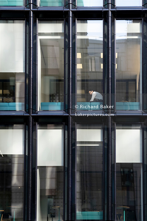 While office workers remain at home in accordance to government Covid guidelines and individual corporate policies, a solitary socially distanced company employee sits alone in the City of London, the capital's financial district, during the third lockdown of the Coronavirus pandemic, on 9th March 2021, in London, England.