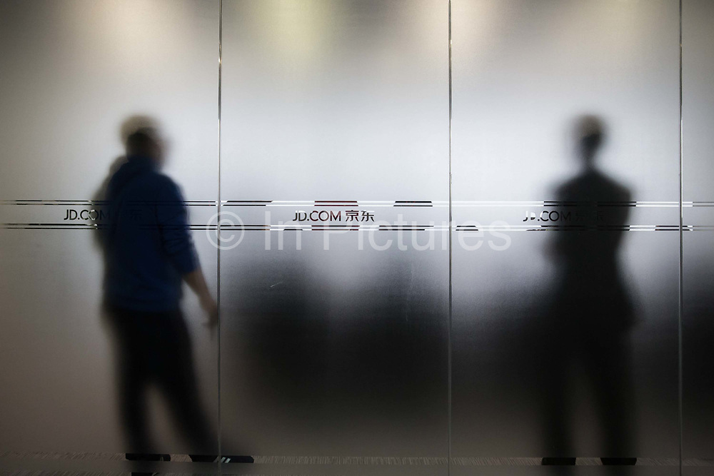 Signages for JD.com Inc. are displayed on a pane of glass of a conference room at JD.coms headquarters in Beijing, China, on Monday, Nov. 30, 2015.  JD.com is Chinas second largest online retailer and is locked in a fierce battle with rival Alibaba.
