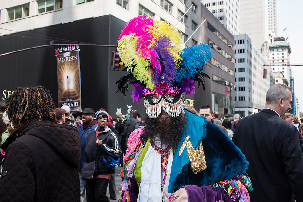 New York, NY, USA-27 March 2016. A man wears a coat and hat of many colors in the annual Easter Bonnet Parade and Festival. Behind him is a banner carried by religious proselytizers.