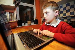 Boy using laptop computer in kitchen MR