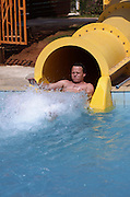 Man shooting out of a water slid tunnel into the pool holding his breath