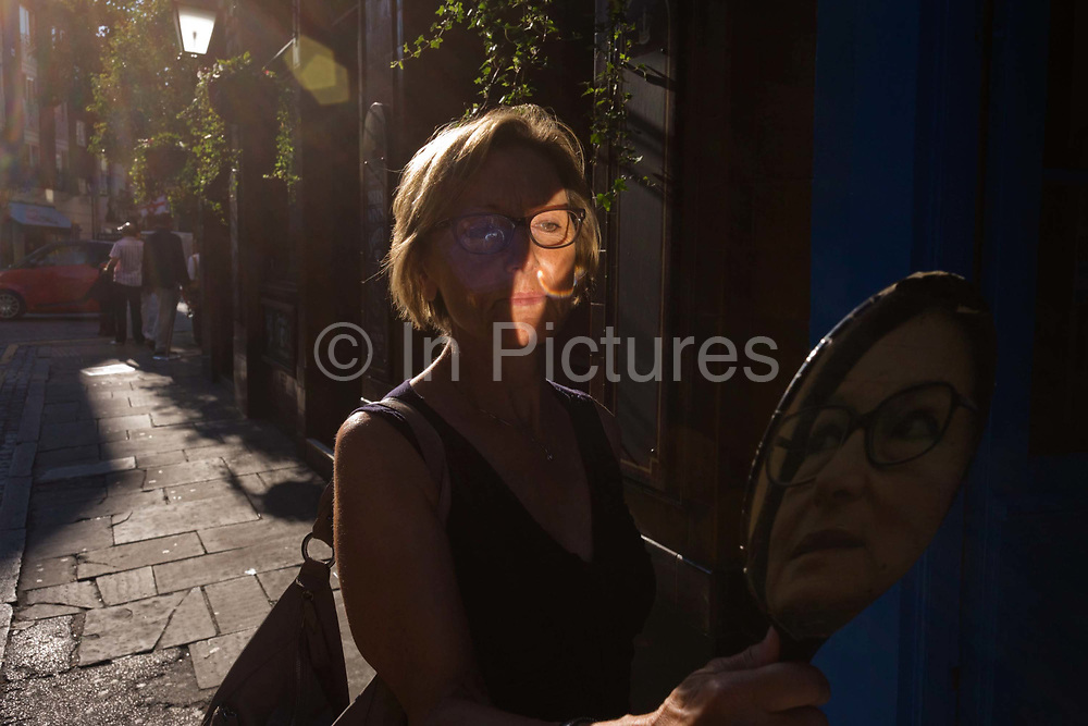 A lady tries on a pair of spectacles using a faced mirror outside a London optician. In afternoon sunshine she looks into the mirror to decide whether to buy or leave them behind. But on the reverse side is another face, not too dissimilar of the female customer.