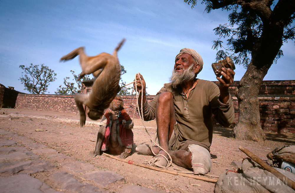 A beggar with a somersaulting monkey.