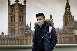 © Licensed to London News Pictures. 11/03/2020. London, UK. A man wearing a medical face mask passes The Houses of Parliament.  It has been reported that Health Minister Nadine Dorries has tested positive for the coronavirus. New cases of the COVID-19 strain of Coronavirus are being reported daily as the government outlines it's plans for controlling the outbreak. Photo credit: Peter Macdiarmid/LNP