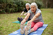 A SENIOR WOMAN STRETCHING WITH FRIENDS