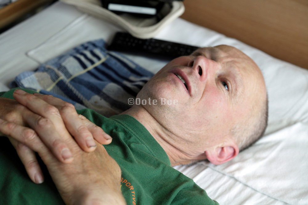 portrait of male person laying on his back in bed