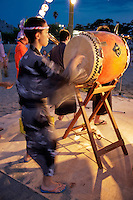 """Taiko Drummer participaing in summer O-bon festivities at Shonan Beach - Taiko means """"drum"""" in Japanese and to the relatively recent art form of ensemble taiko drumming or more specifically """"kumi-daiko"""".  Performances can last up to 25 minutes and typically follow a rapid/ sudden/urgent structure; the performance speeds up significantly towards the grand finale."""