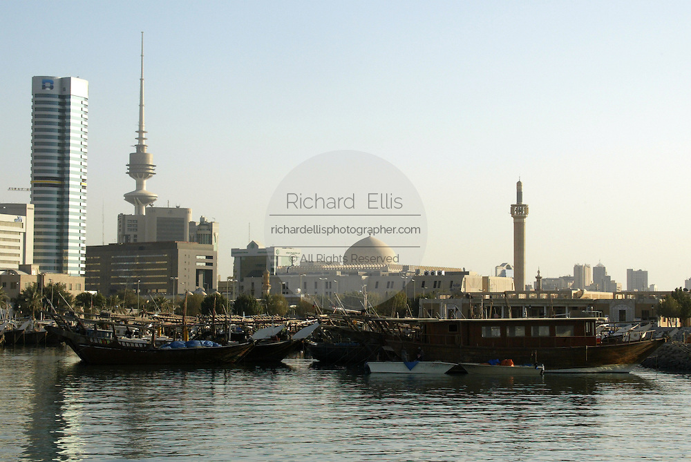 Ancient doha fishing boats along the waterfront of the Persian Gulf with the skyline of Kuwait City.