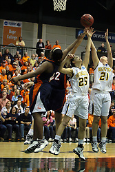 19 March 2010: Philana Greene, Caroline Bernal-Silva and Melissa Alwardt reach for the same loose ball. The Flying Dutch of Hope College defeat the Yellowjackets of the University of Rochester in the semi-final round of the Division 3 Women's Basketball Championship by a score of 86-75 at the Shirk Center at Illinois Wesleyan in Bloomington Illinois.