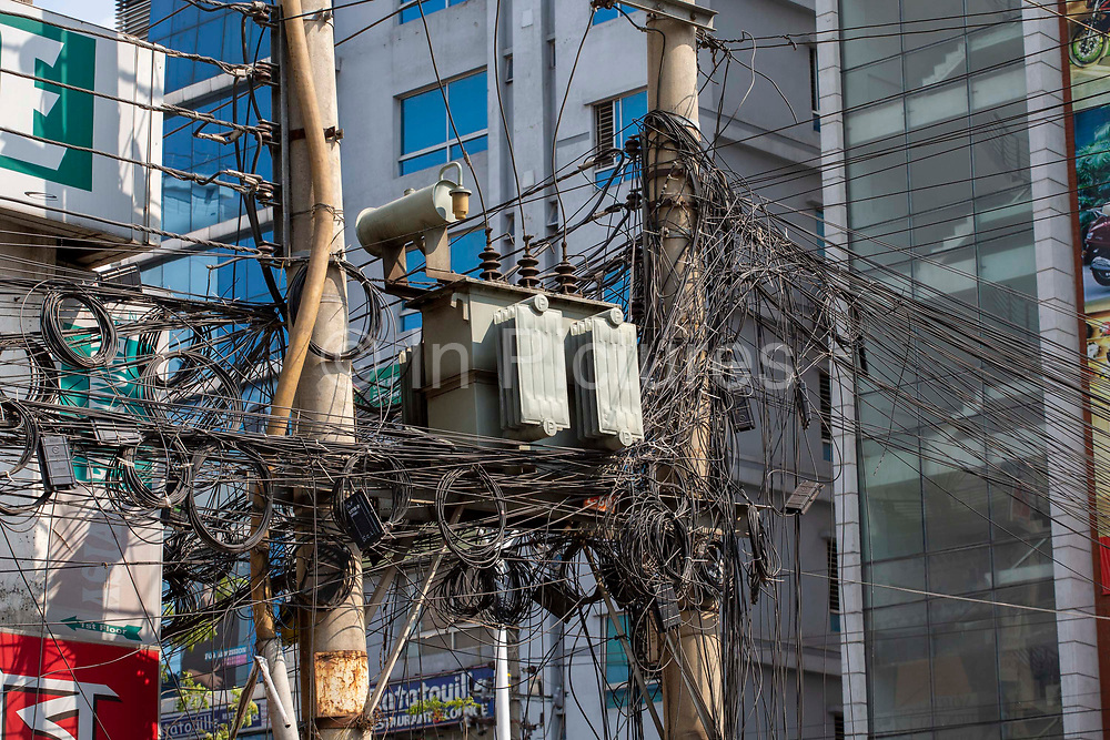 A chaotic electricity transformer box surrounded by wires and cables up a pylon on the street in Tejgaon railway district of Dhaka on the 2nd of October 2018 in Dhaka, Bangladesh.