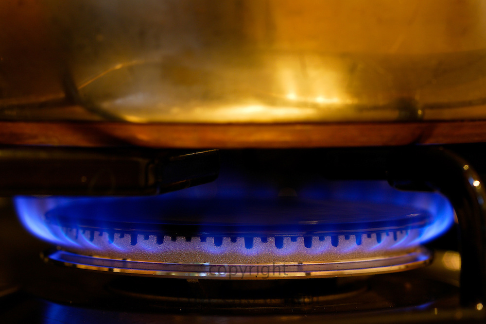 Saucepan cooking over gas flame on cooker hob, England, United Kingdom