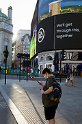 With a further 149 reported dying from Coronavirus in the last 24hrs, taking the UK death toll to 43,320, shoppers walk past digital advertising in Piccadilly Circus during the Covid pandemic, on 25th June 2020, in London, England.