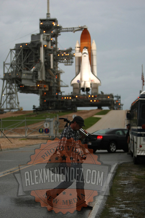A photographer walks back to the media bus as the Shuttle Atlantis rests atop the launch pad at Kennedy Space Center Thursday, July 7, 2011, in Cape Canaveral, Fla. Shuttle Atlantis is scheduled to launch on Friday, July 8 and is the 135th and final space shuttle launch for NASA..  (AP Photo/Alex Menendez)