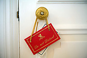 A 'Do not disturb' sign hanging on a doorknob at the Ritz Hotel, London