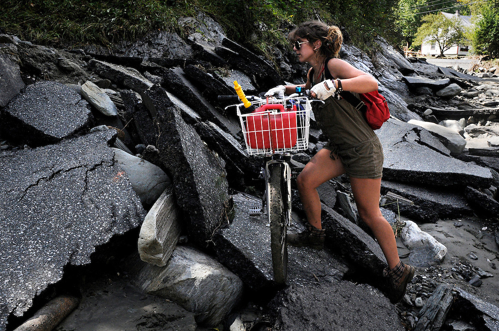 Willow Griffith of Bethel picks her way through chunks of asphalt that have come to rest on bedrock where Camp Brook Road used to be in Bethel Tuesday, August 30, 2011. <br /> Valley News - James M. Patterson<br /> jpatterson@vnews.com<br /> photo@vnews.com