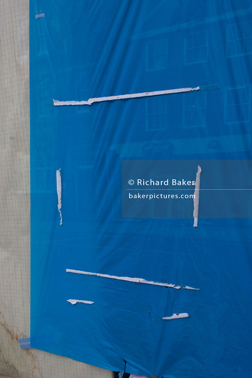 Blue paper, glue remnants and Damp stains on a card business window in an East Grinstead street in Sussex, a victim of the UK recession. Around a recession-bled Britain, high-street businesses have been going bust in their thousands. Britain has now endured eight recessions since the Second World War. No two recessions are alike, and that applies to the current slowdown also. It has been caused by a shock to the availability of credit, a massive build up of debt. The number of people out of work currently stands at almost two million. Given the rate at which the economy is deteriorating this could easily be above three million. From a continuing piece of work about windows and urban messages, the picture is from the project of closed business windows: 'Bust - the Art of Recession'.