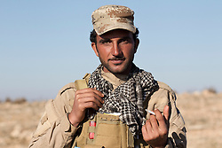 © Licensed to London News Pictures. 11/12/2014. Sinjar Mountains, Iraq. A Yazidi fighter smokes a cigarette as he waits for Iraqi Air Force helicopters to bring supplies and evacuate some of the refugees on the top of Mount Sinjar.<br /> <br /> Although a well publicised exodus of Yazidi refugees took place from Mount Sinjar in August 2014 many still remain on top of the 75 km long ridge-line, with estimates varying from 2000-8000 people, after a corridor kept open by Syrian-Kurdish YPG fighters collapsed during an Islamic State offensive. The mountain is now surrounded on all sides with winter closing in, the only chance of escape or supply being by Iraqi Air Force helicopters. Photo credit: Matt Cetti-Roberts/LNP