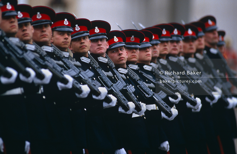 Seventeen officer cadets march in line wearing full dress uniform with their rifles on shoulders past guests and VIPs at their passing out parade in the Royal Military Academy Sandhurst. The recently-graduated soldiers march in a near-perfect line looking over their right shoulders towards their commanding officers and VIP guests which sometimes includes Her Majesty the Queen. We see every face clearly and notice their different heights and sizes.  Sharp focus is centred on the smallest man in the parade. The Royal Military Academy Sandhurst (RMAS), commonly known simply as Sandhurst, is the British Army officer initial training centre. Sandhurst is prestigious and has had many famous alumni including Sir Winston Churchill, King Abdullah II of Jordan, Sultan Qaboos of Oman and, more recently, Prince Harry and Prince William. All British Army officers, and many from elsewhere in the world, are trained at Sandhurst. RMA Sandhurst was formed in 1947, from a merger of the Royal Military Academy in Woolwich (which trained officers for the Royal Artillery and Royal Engineers from 1741 to 1939) and the Royal Military College at Sandhurst.