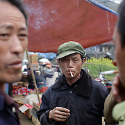 Men smoking at the Lung Khau Nhin Market. Vietnam. Lung Khau Nhin Market is rural tribal market hiding itself amongst the mountains and forests of the far north Vietnam about 10 km from the border with China. The market plays an important role for the local ethnic people, Flower Hmong, Black Zao, Zay, and very small ethnic groups  Pa Zi, Tou Zi, Tou Lao. Tourist trips to the market run from Sapa and Lao Cai every week. Lung Khau Nhin Market, Vietnam.15th March 2012. Photo Tim Clayton