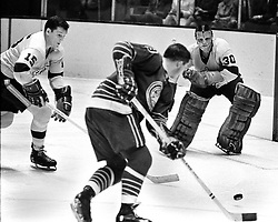 Seals #9 Bill Hicke takes a shot at Kings goalie #30 Terry Sawchuk, #15 Ted Irvine..(1967 hockey action. photo/Ron Riesterer)