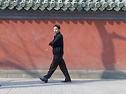 person walking along the wall of an old temple China Beijing