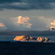 The setting sun, very low on the horizon, catches steep mountains near Hughes Bay on the Antarctic Peninsula.