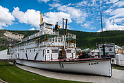 Preserved historic 1922-1951 sternwheel paddle steamer, SS Keno National Historic Site of Canada, at dry dock along the Yukon River in Dawson City, Yukon, Canada. The vessel was built in 1922 in Whitehorse by the British Yukon Navigation Company, a subsidiary of the White Pass and Yukon Route railway company. It mostly transported silver, zinc and lead ore down the Stewart River from mines in the Mayo district to the confluence of the Yukon and Stewart rivers at Stewart City. It was retired from commercial service in 1951 due to the extension and improvement of the Klondike Highway in the years after World War II. About 250 sternwheelers served the Yukon River and its tributaries. Dawson City was the center of the Klondike Gold Rush (1896–99), after which population rapidly declined. Dawson City shrank further during World War II after the Alaska Highway bypassed it 300 miles (480 km) to the south using Whitehorse as a hub. In 1953, Whitehorse replaced Dawson City as Yukon Territory's capital. Dawson City's population dropped to 600–900 through the 1960s-1970s, but later increased as high gold prices made modern placer mining operations profitable and tourism was promoted. In Yukon, the Klondike Highway is marked as Yukon Highway 2 to Dawson City.