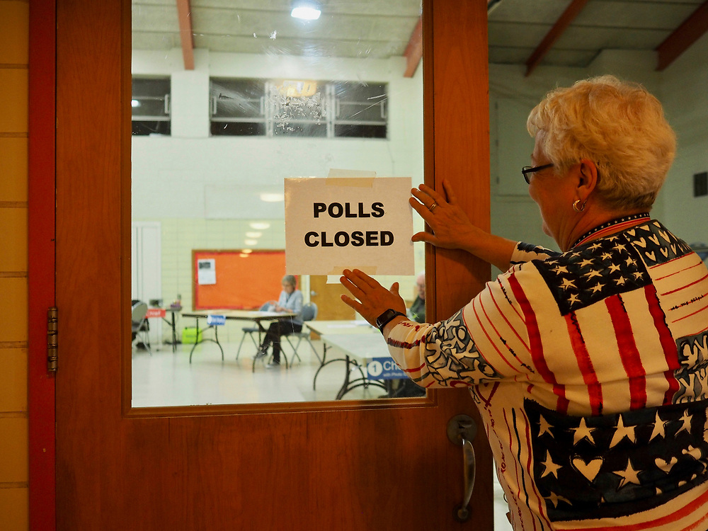 Election Chief places Polls Closed sign on the doors at the end of Election Day, November 5, 2019