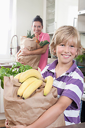 Boy with his mother holding bags of groceries in kitchen, Bavaria, Germany
