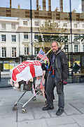 A portrait of a homeless man and his shopping trolley with St Georges Cross Flag and American Flag on the 13th July 2018 in London in the United Kingdom.
