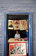 A man sells revolutionary posters in Dashanzi. China's art scene is becoming popular among foreign art collectors pushing prices higher.