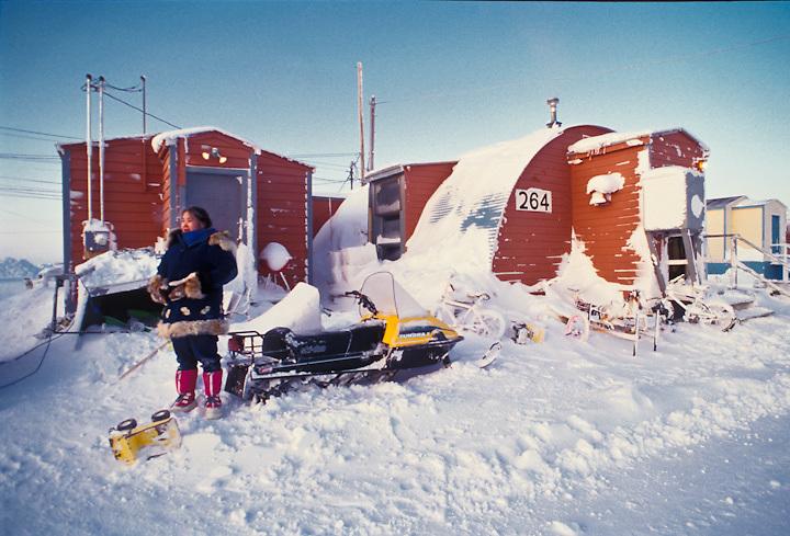 A woman awaits transportation near dwellings in the Iñupiat  village of Barrow, Alaska.