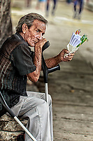Senior's Resignation:  A crippled senior citizen passes another lonely day selling small packets of candy to supplement his inadequate pension, Havana Cuba.