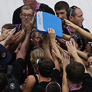 The USA swim team huddle on the pool deck before their first swim training at the Aquatic Centre at Olympic Park, Stratford during the London 2012 Olympic games preparation at the London Olympics. London, UK. 23rd July 2012. Photo Tim Clayton