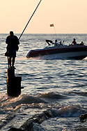 At sunset, a fisherman on the Beirut Corniche stands on a post as a speedboat flying a Lebanese flag cruises past.