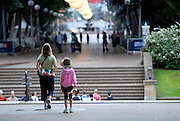 Mother and daughter (6 years old) strolling through the fig tree lined avenue in Hyde Park. Sydney, Australia
