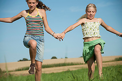 Two carefree happy young girls running meadow