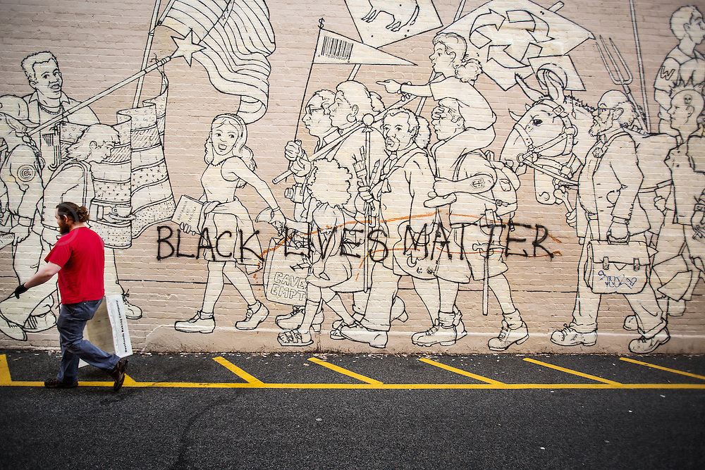 """A United States Postal Service employee, who did not want to be identified by name, walks past the mural named """"Parade of Humanity"""", painted by Michael Brown and located on the side of the Carolina Coffee House, Chapel Hill, on Dec. 16."""