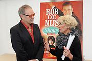 """DVD presentatie """"De Rob de Nijs Shows"""".Op deze dvd staan de 3 bewaard gebleven tv-shows met dezelfde naam. In de periode 1964-1966 maakte Rob de Nijs deze TV-shows voor de Vara .<br /> <br /> Op de foto: Anneke Grönloh geeft aan haar oude vriend Rob de Nijs het eerste exemplaar van de dvd De Rob de Nijs Shows"""