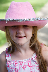 Little girl wearing a hat smiling,