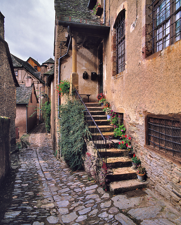 Potted flowers line the steps to a residence in Conques in the Lot River Valley in France.