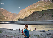 Children playing along the Amu Daria river in Tajikistan, Afghanistan is across on the other side.
