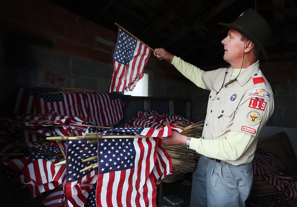 Assistant Scout Master Ray Fye prepares flags before scouts from Troop 119 arrive Wednesday at Veterans Cemetery in Grand Island. About 1,500 flags were placed at the cemetery in preparations for Memorial Day. (Independent/Matt Dixon)