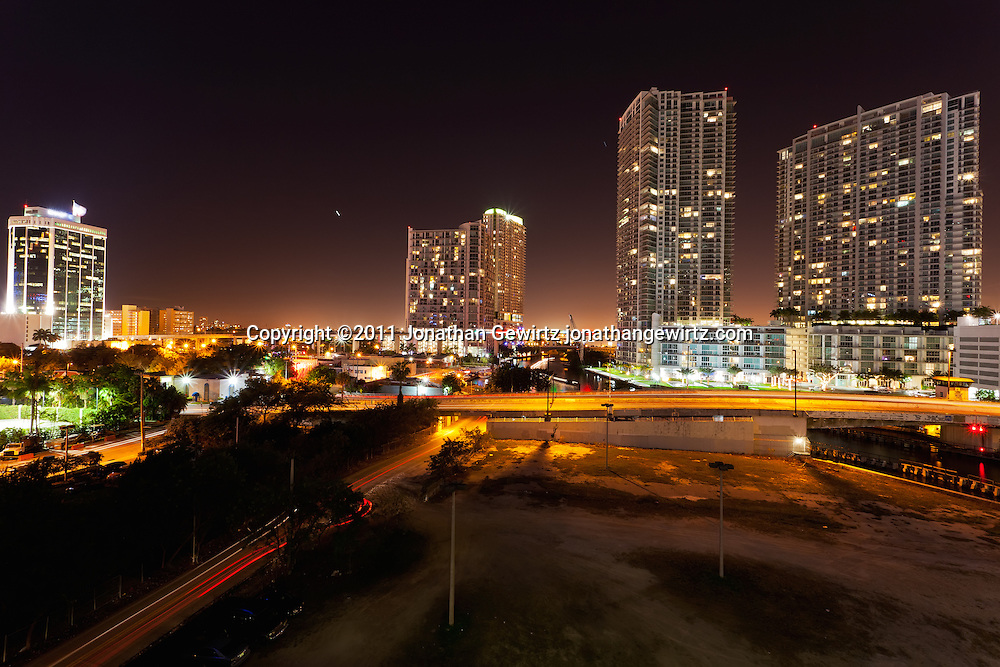 Night view of Miami's downtown and Brickell area just south of the Miami River, showing the South Miami Avenue drawbridge, highrise condo, office and rental apartment buildings, and the Metrorail elevated track and colored lights. WATERMARKS WILL NOT APPEAR ON PRINTS OR LICENSED IMAGES.