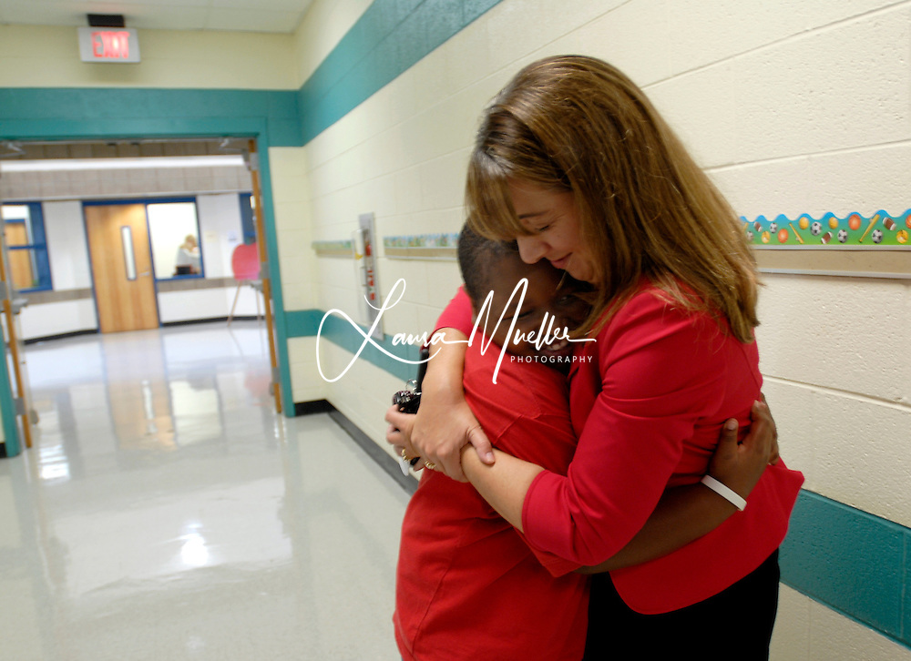8/25/09 Tariq, 10, a 5th grader at Smithfield Elementary School gets a hug from Assistant Principal Danielle Miller.Tariq has been very involved in the school's green initiative, collecting 227 large garbage bags full of plastic bags for recycling.  L.MUELLER/The Charlotte Observer
