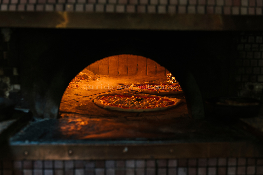 NAPLES, ITALY - 1 AUGUST 2018: Pizzas are baked in the pizza oven here at Cantina del Gallo, a family-owned restaurant in the Rione Sanità in Naples, Italy, on August 1st 2018.<br /> <br /> Cantina del Gallo, in the Rione Sanità, was established in 1898 and run by four generations of the Silvestri family. The cantina began as a store selling bulk wine and oil. It was only in the 1950s, when the legendary Aunt Cuncetta began cooking, that it became the simple and genuine tavern it is today.<br /> There are three dishes that are the restaurant's workhorses, and the ones we always seem to rotate between: the pennette alla sorrentina (a variation of the classic gnocchi alla sorrentina, seasoned with tomato, basil and stringy mozzarella), the baked cod (although the fried cod is just as mouth-watering) and the pizza cafona (peasant pizza), topped with oregano, cheese, chile and with double the tomatoes (tomato juice and chopped tomatoes).