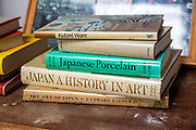Books on Japanese art an ceramics on display in house clearance auction sale room, UK