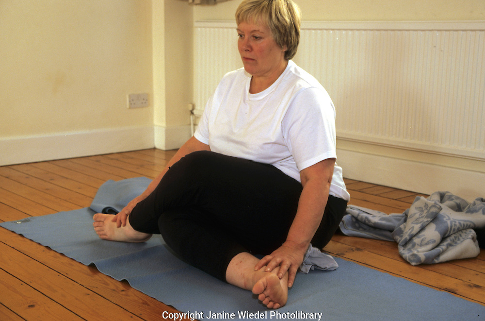 Woman in lotus position in Yoga class..